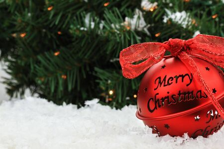 Beautiful red Christmas bell ornament lies in the snow with copyspace and a message of &quot,Merry Christmas.&quot,