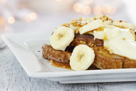French toast topped with sliced bananas, nuts, cream cheese sauce and caramel syrup. Extreme shallow depth of field with selective focus.