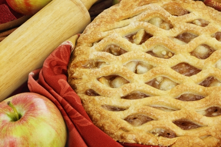 Delicious fresh baked apple pie with rolling pin and ingredients. Perfect for the holidays.