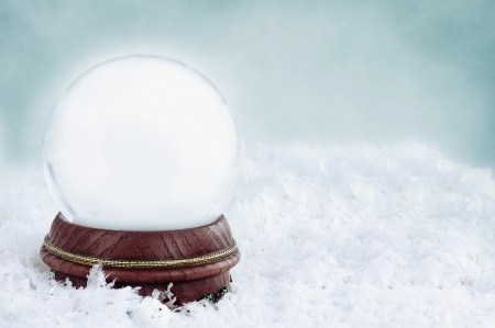 Blank snow globe with with copy space available against a blue background.