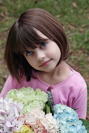 Beautiful little girl witha  bunch of pastel colored Hydrangeas for her mother on Mother's Day.