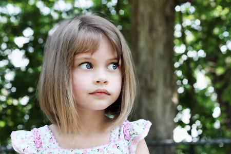 Cute little girl with bobbed hair cut looking away from camera. Extreme shallow depth of field.