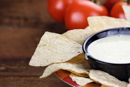 Queso Blanco or White Cheese Sauce with corn tortilla chips and fresh tomatoes. Extreme shallow depth of field with selective focus on cheese dip.