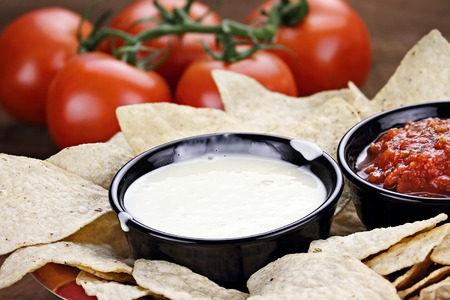 Queso Blanco or White Cheese Sauce with corn tortilla chips, salsa and fresh tomatoes. Shallow depth of field with selective focus on cheese dip.