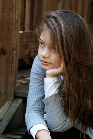 Young girl sitting on porch steps with long hair falling loosely around her face. Extreme shallow depth of field.