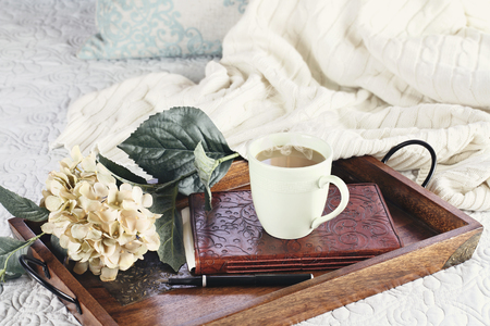 Photo for A hot relaxing cup of coffee with a book and flowers in a serving tray sitting on a comfortable bed with blanket. Extreme shallow depth of field. - Royalty Free Image