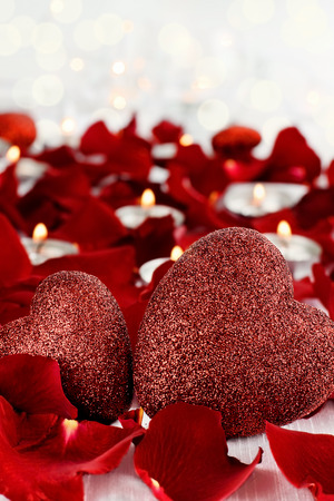 Photo pour Valentine's Day hearts surrounded by rose petals and lite candles against a white background. Room for copy space with extreme shallow depth of field. - image libre de droit