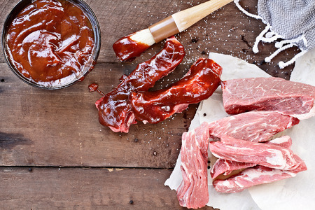 Foto für Country ribs with barbecue sauce and basting brush over a rustic table. - Lizenzfreies Bild