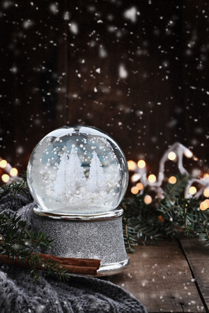 Rustic image of a snow globe surrounded by pine branches, cinnamon sticks and a warm gray scarf with gently falling snow flakes.