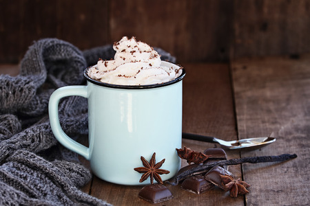 Photo for Enamel cup of hot cocoa or coffee for Christmas with whipped cream, shaved chocolate, vanilla pod, spices and gray scarf against a rustic background. Shallow depth of field with selective focus on drink. - Royalty Free Image
