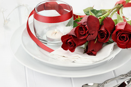 Photo pour Romantic candlelite table setting with long stem red roses and candles in the background. Shallow depth of field with selective focus on roses. - image libre de droit