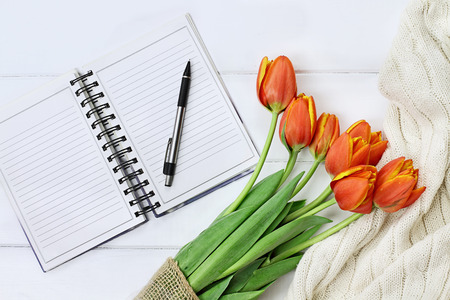 Photo pour Overhead shot a bouquet of orange and yellow tulips and a cozy knit throw blanket over white wood table top with an open book and pen ready to journal. Flat lay top view style. - image libre de droit