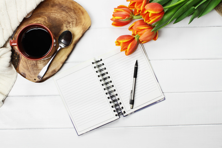 Photo pour Overhead shot a cup of coffee, open book, knit throw blanket and a bouquet of orange and yellow tulip flowers over white wood table top. Flat lay top view style. - image libre de droit
