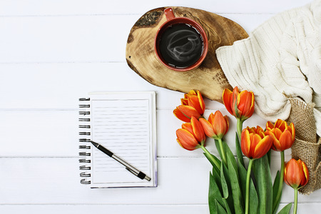 Foto de Overhead shot a blank notebook with pen, coffee and a bouquet of orange and yellow tulips over a wood table. Flat lay top view style. - Imagen libre de derechos