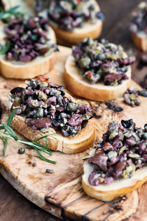 Foto de Homemade mixed Olive Tapenade made with garlic, capers, olive oil, Kalamata, black and green olives spread over toasted bread. Extreme shallow depth of field with selective focus on center canape. - Imagen libre de derechos