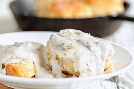 Photo pour American biscuits from scratch covered with thick white sausage gravy. Selective focus with cast iron skillet / pan in the background over a white table. - image libre de droit