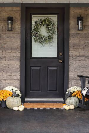 Photo for Front porch decorated for Thanksgiving Day with homemade wreath hanging on door. Heirloom gourds,  white pumpkins, and mums giving an inviting atmosphere. - Royalty Free Image