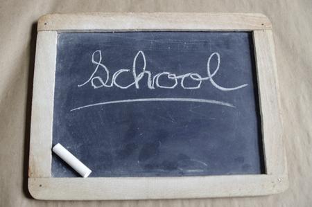 Cursive word school on black chalk board with white chalk