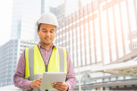 Photo pour Engineer with hardhat is holding a tablet computer. Construction manager concept. - image libre de droit