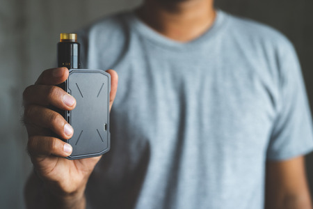 Photo for Young man holding electronic cigarette. - Royalty Free Image