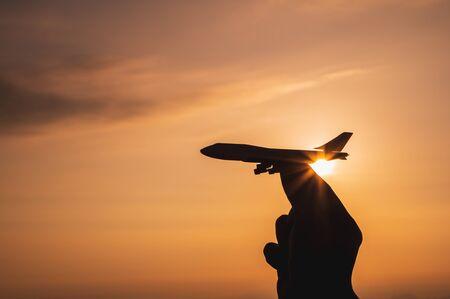 Photo pour A hand holding a toy plane Go to the sky with sunset light - image libre de droit