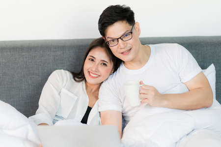 Photo for Young asian couple love man and woman watching movie in laptop on the bed in the morning. Happy moment concept. - Royalty Free Image