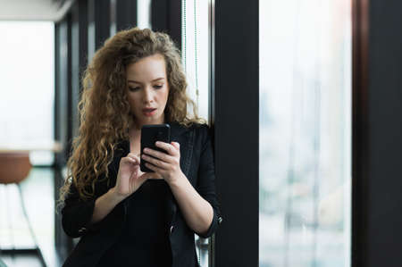 Photo for Beautiful sexy woman using smartphone standing near window in office. - Royalty Free Image