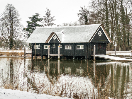 Breukelen, Netherlands - 2010-02-14: Wooden boathouse with thatched roof covered with a thin layer of snow, at the shore of River Vecht. Boathouse of Nijenrode rowing-club 'het Galjoen'. Straatweg 60, 3621 BR Breukelen, Rijksmonument nummer: 520614
