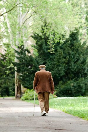 Elderly man uses a cane to assist him with walking. He is getting some exercise at the park.