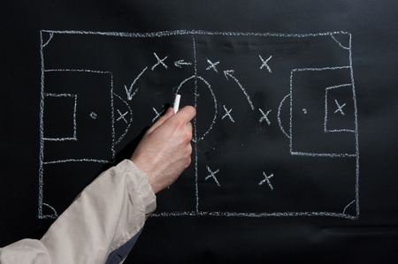 Photo pour Man drawing a soccer game tactics and strategy with white chalk on a blackboard  - image libre de droit