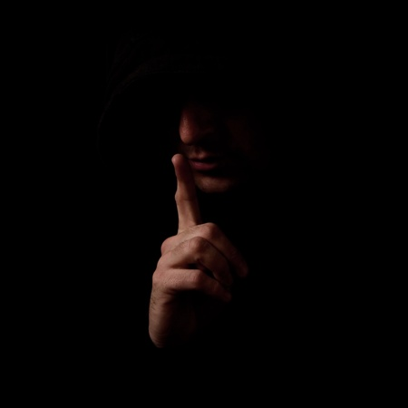 Man in the low light interior holding index finger over his mouth, making a Shh gesture