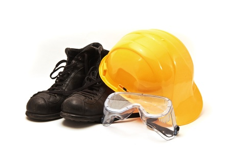 Yellow hard hat, old leather boots and protective goggles, protective equipment in construction industry.