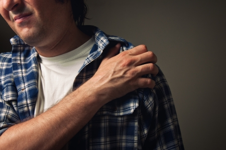 Young adult man suffering from severe shoulder pain