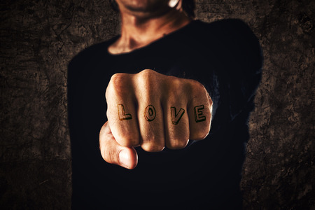 Love tattoo. Hand with clenched fist on dark background. Power, determination, resistance concept.