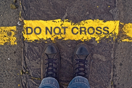 Photo for Male sneakers on the asphalt road with yellow line and title Do Not Cross. Border line concept, danger or warning sign. - Royalty Free Image