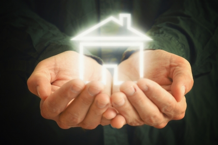 House in hands of a man  Man holding house in cupped hands  House selling or home insurance concept