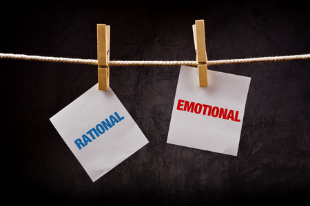 Rational vs Emotional concept. Words printed on note paper and attached to rope with clothes pins.