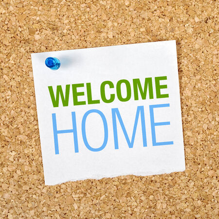 Welcome Home Message on Reminder Paper pinned to a Cork Memory Board