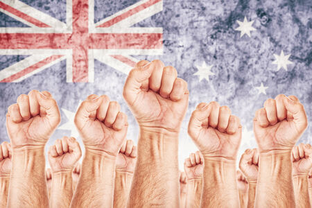 Australia Labour movement, workers union strike concept with male fists raised in the air fighting for their rights, Australian national flag in out of focus background.