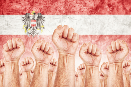 Austria Labour movement, workers union strike concept with male fists raised in the air fighting for their rights, Austrian national flag in out of focus background.