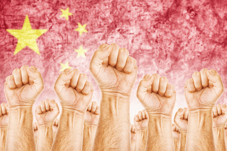 China Labour movement, workers union strike concept with male fists raised in the air fighting for their rights, Chinese national flag in out of focus background.