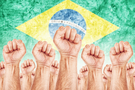 Brasil Labour movement, workers union strike concept with male fists raised in the air fighting for their rights, Brasilian national flag in out of focus background.