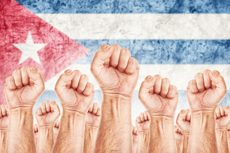 Cuba Labour movement, workers union strike concept with male fists raised in the air fighting for their rights, Cuban national flag in out of focus background.