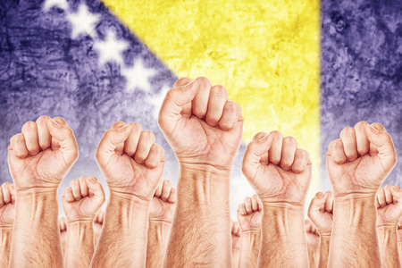 Bosnia and Herzegovina Labour movement, workers union strike concept with male fists raised in the air fighting for their rights, Bosnian national flag in out of focus background.