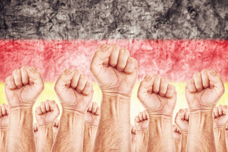 Germany Labour movement, workers union strike concept with male fists raised in the air fighting for their rights, German national flag in out of focus background.