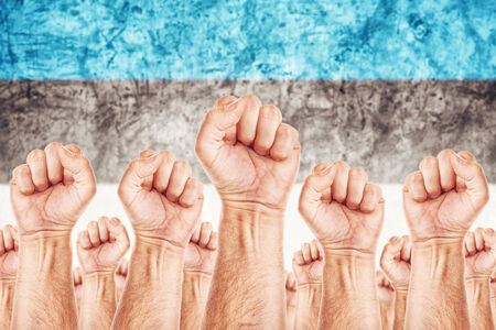Estonia Labour movement, workers union strike concept with male fists raised in the air fighting for their rights, Estonian national flag in out of focus background.
