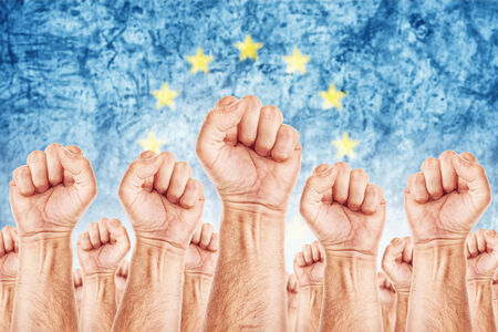 Europe Labour movement, workers union strike concept with male fists raised in the air fighting for their rights, European Union flag in out of focus background.