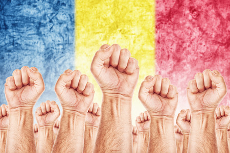 Romania Labour movement, workers union strike concept with male fists raised in the air fighting for their rights, Romanian national flag in out of focus background.