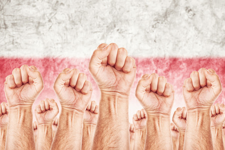 Poland Labour movement, workers union strike concept with male fists raised in the air fighting for their rights, Polish national flag in out of focus background.