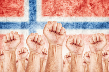 Norway Labour movement, workers union strike concept with male fists raised in the air fighting for their rights, Norwegian national flag in out of focus background.
